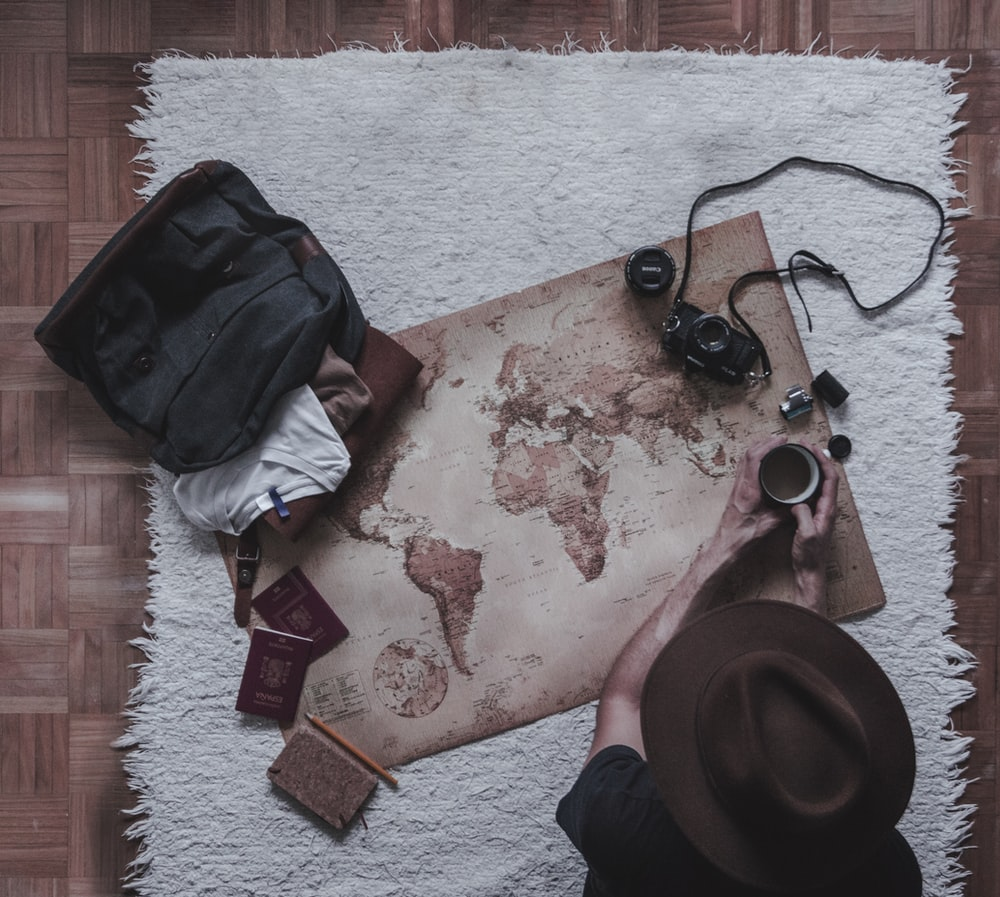 person holding mug sitting beside map