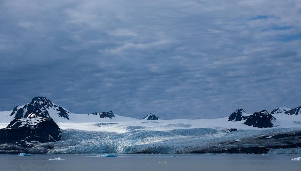mountain range beside sea under clear blue sky