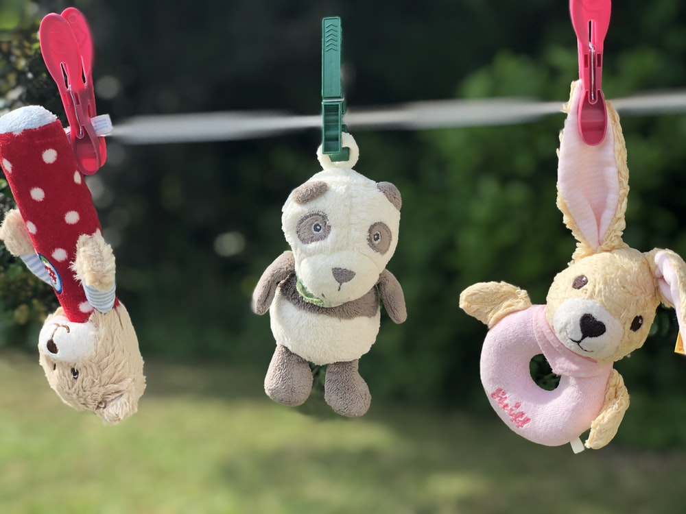 three assorted-colored animal plush toys hanging