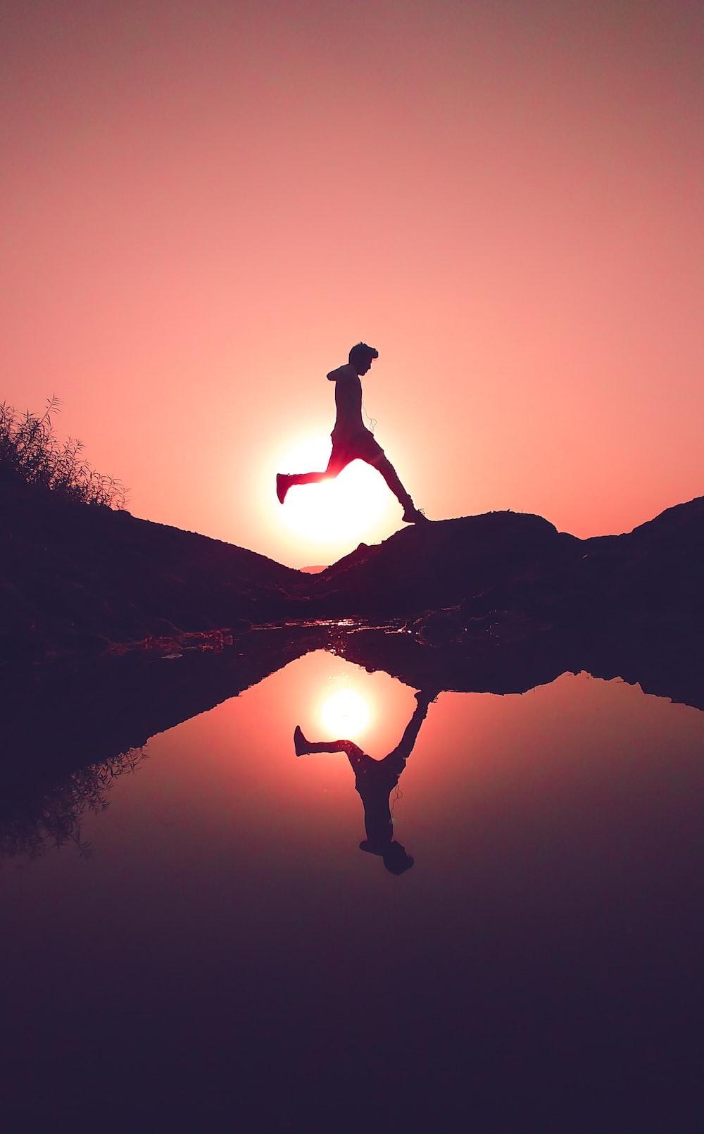 man jumping on rock beside lake