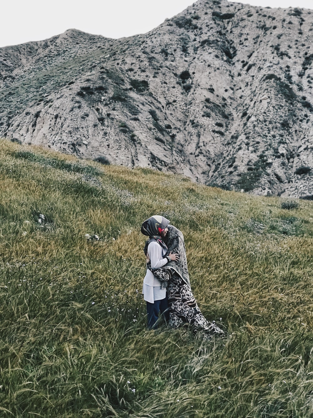 two person standing and hugging in green field beside mountain