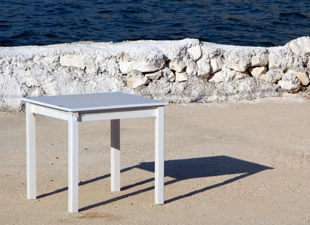 square white wooden table on dirt ground