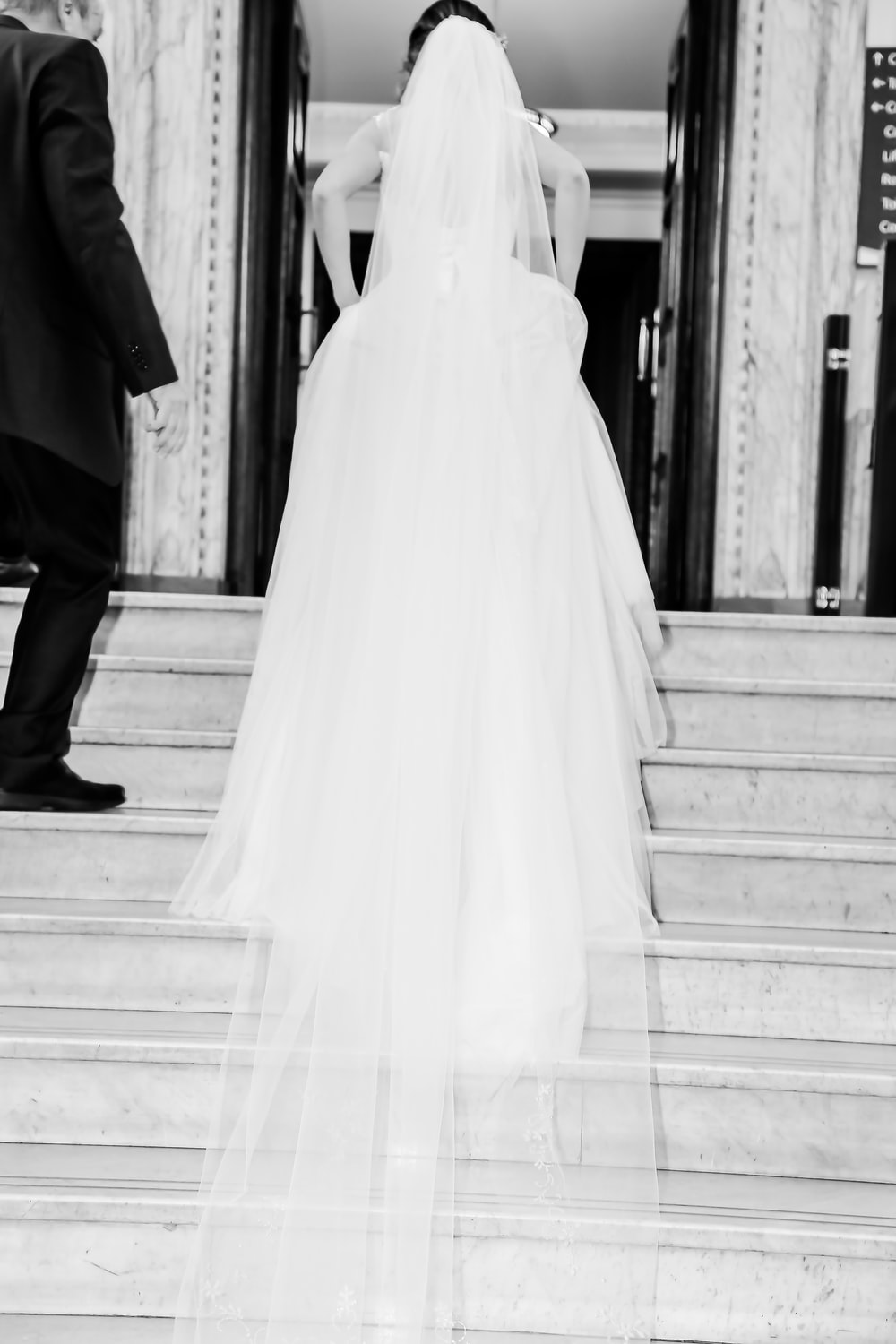 woman in wedding dress waking on stairs