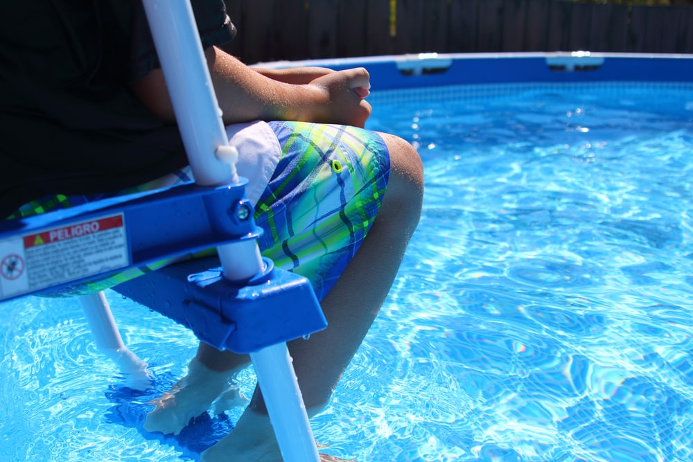 person sitting on pool ladder