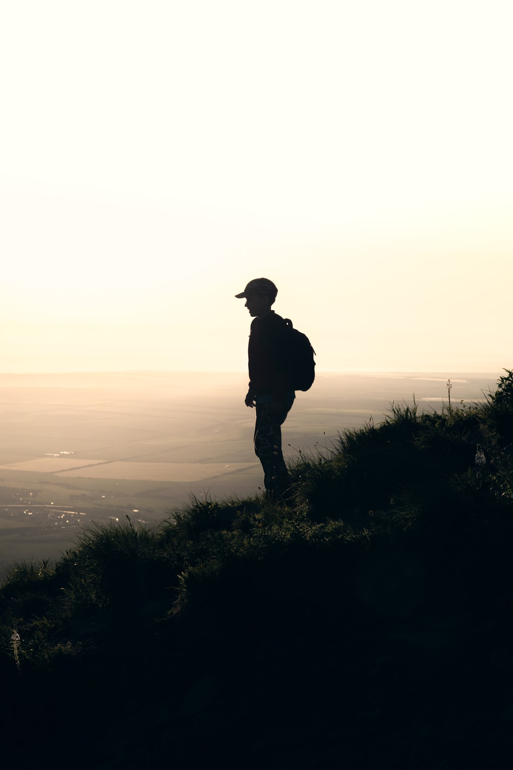 silhouette of man with backpack standing on slope of hill at dusk