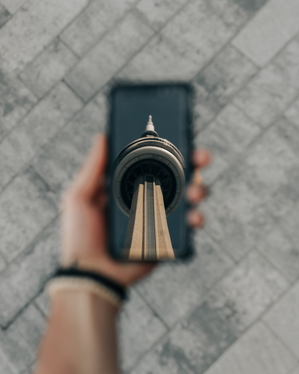 person holding CN Tower print phone case