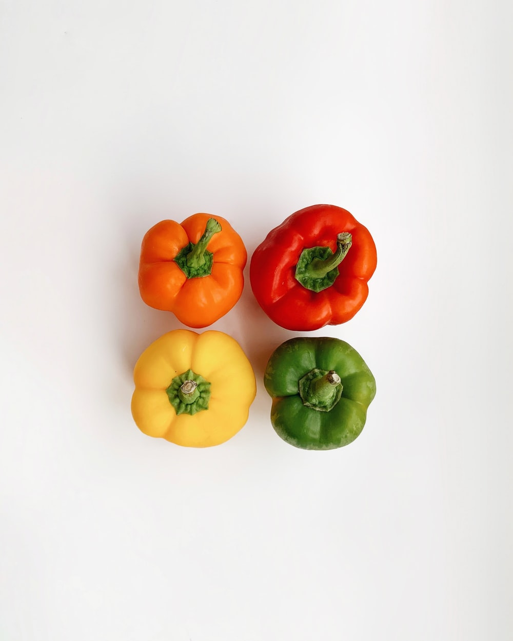 four assorted-colored bell peppers