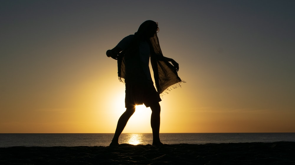 silhouette photo of person wearing black scarf