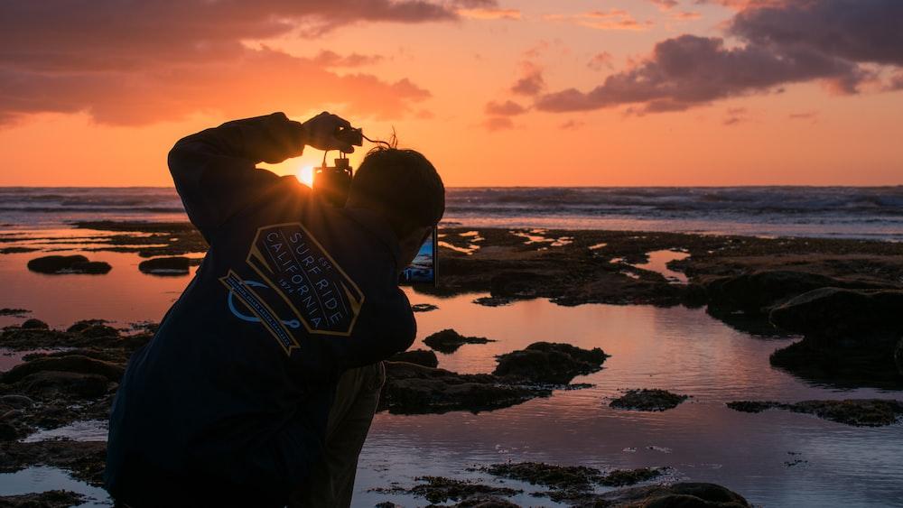 man standing beside sea during sunset