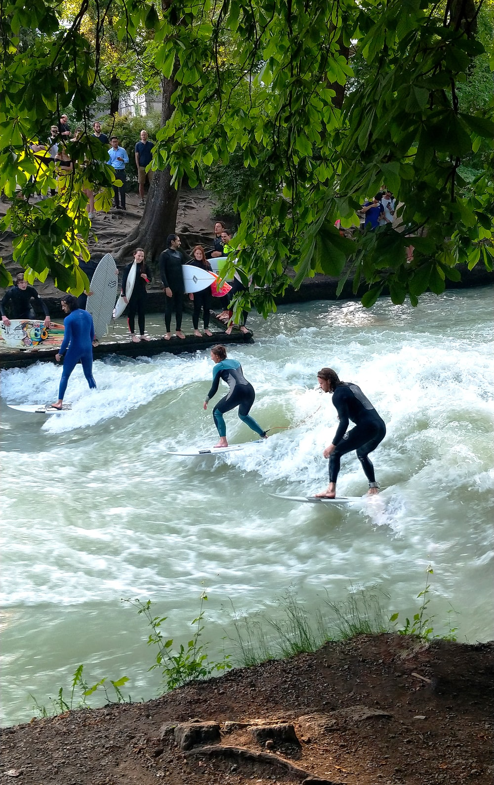 three person surfing in water during daytime
