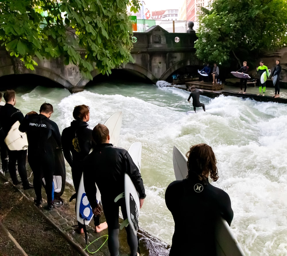 group of people holding surfboards at the river