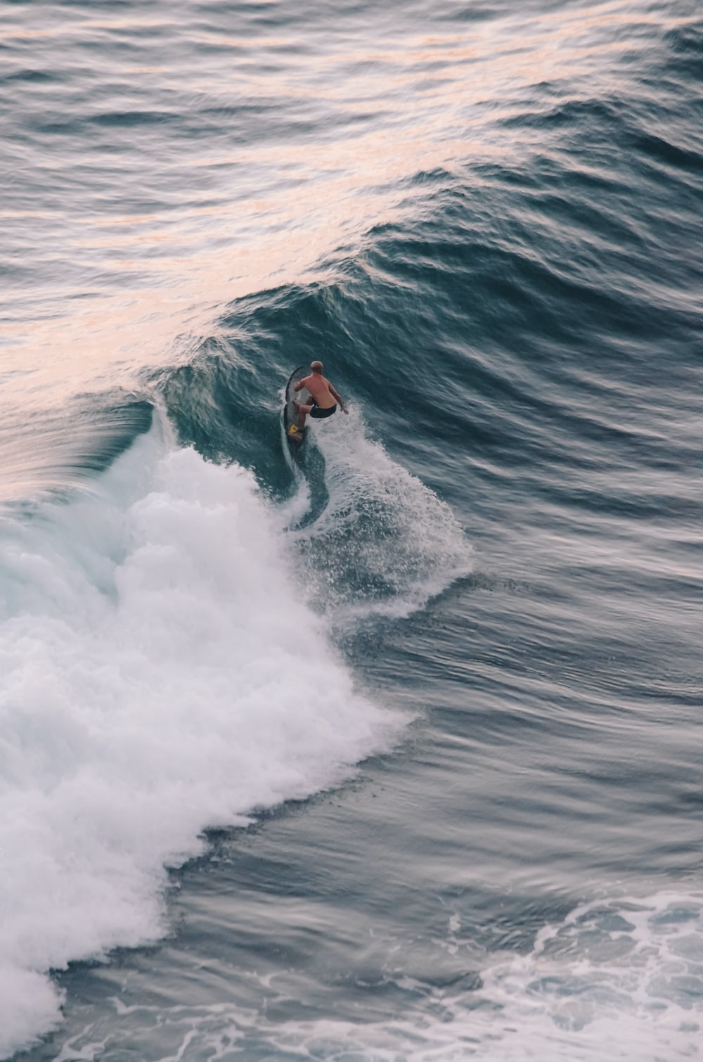 person surfing in a wave close-up photography