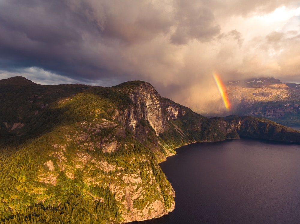 body of water near mountain with rainbow during daytime