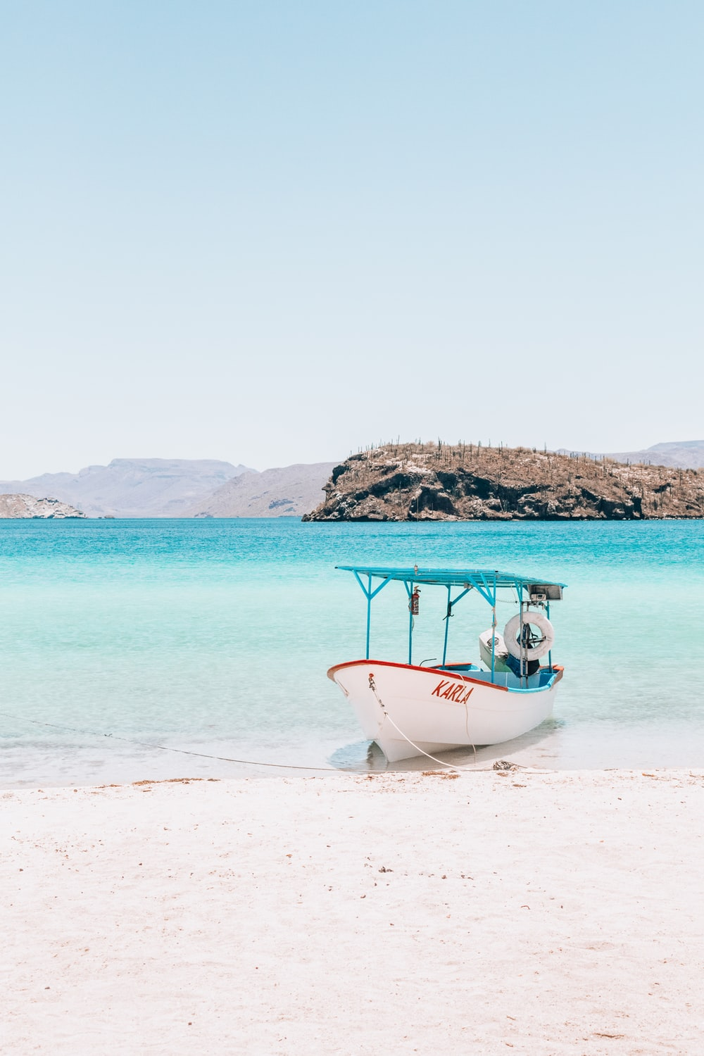 person riding on white boat on seashore