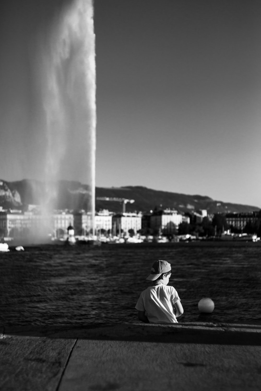 grayscale photography of boy sitting beside body of water