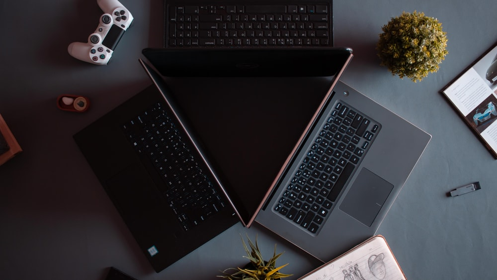 three black and grey laptops