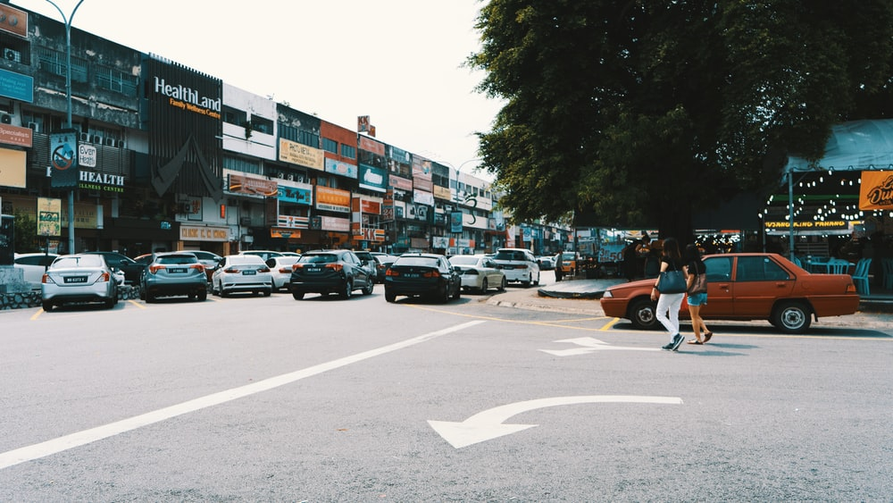 woman walking beside red sedan