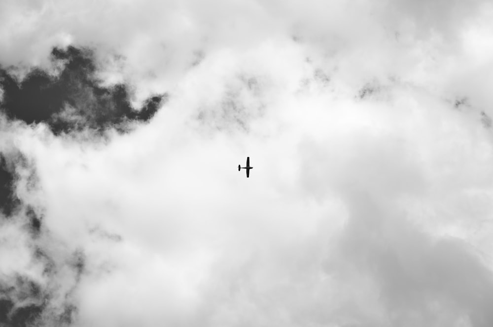 silhouette of airplane under white clouds