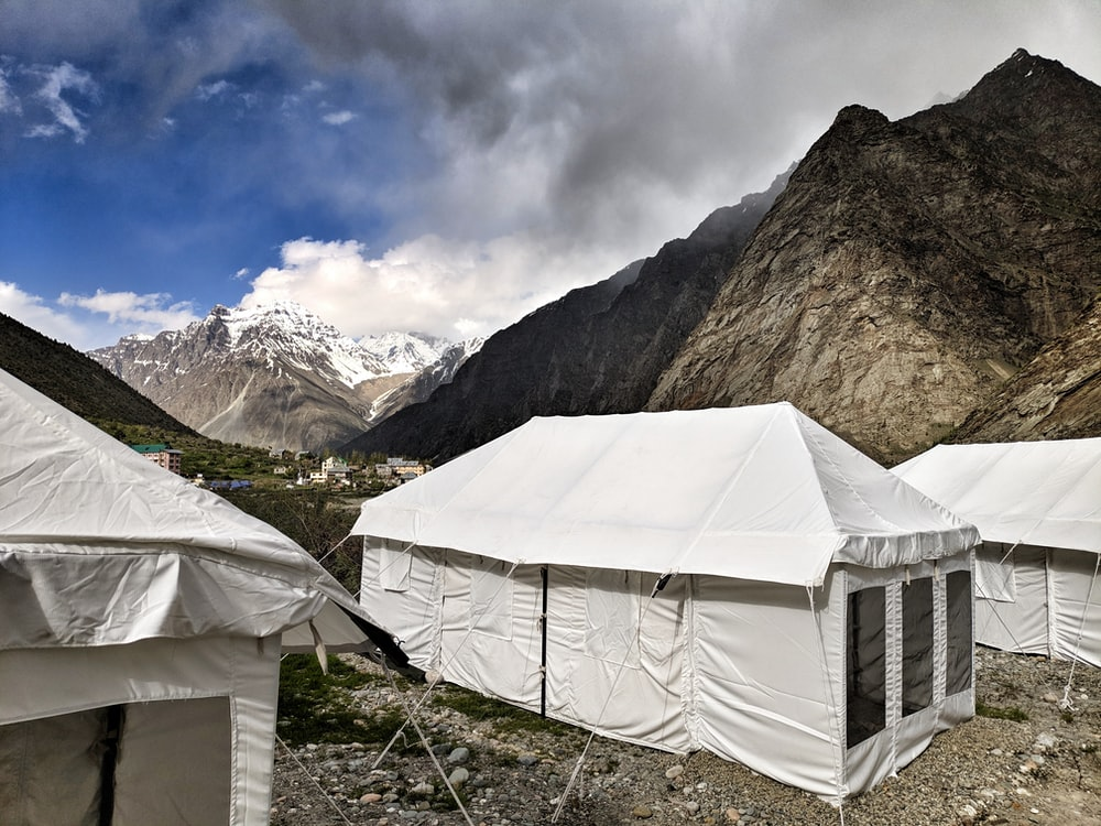 white tent near rock formation during daytime