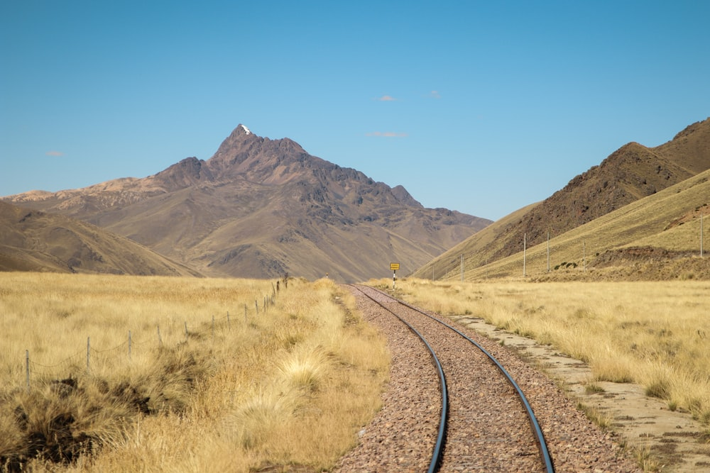 train track near mountains during day