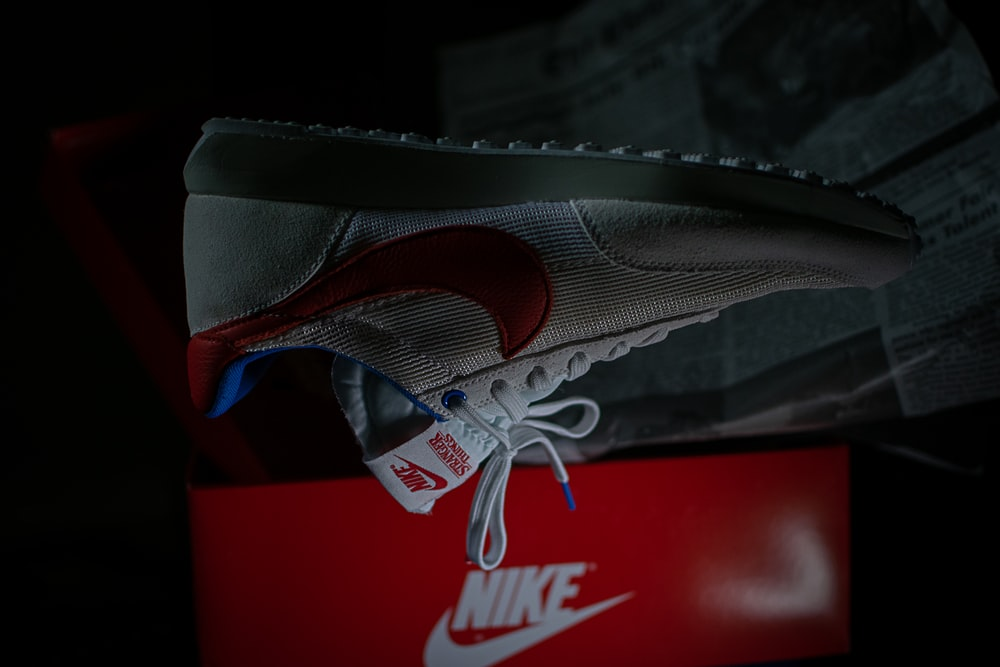 unpaired white and red Nike shoe
