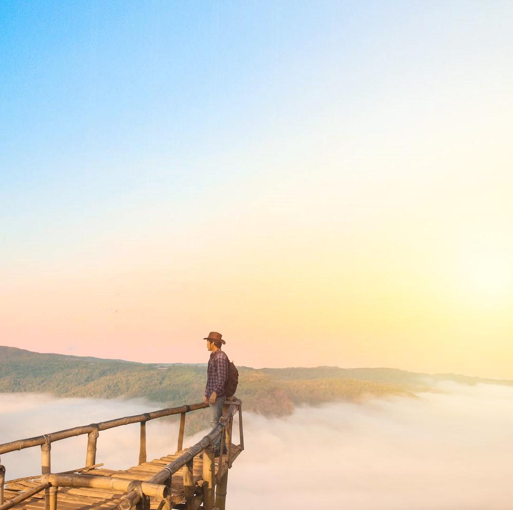 man standing on edge during daytime