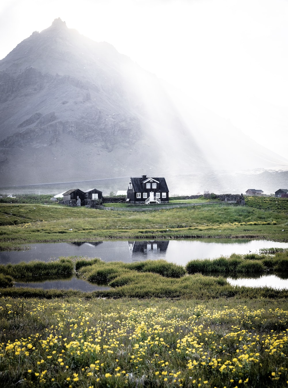 black house near body of water with mountain at distance