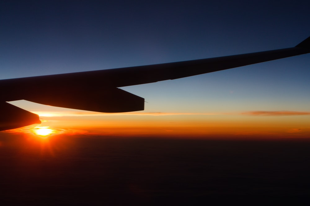 silhouette of airplane wing at sunset