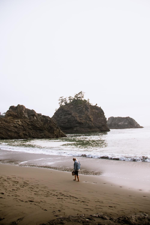 man walking on seashore under white sky