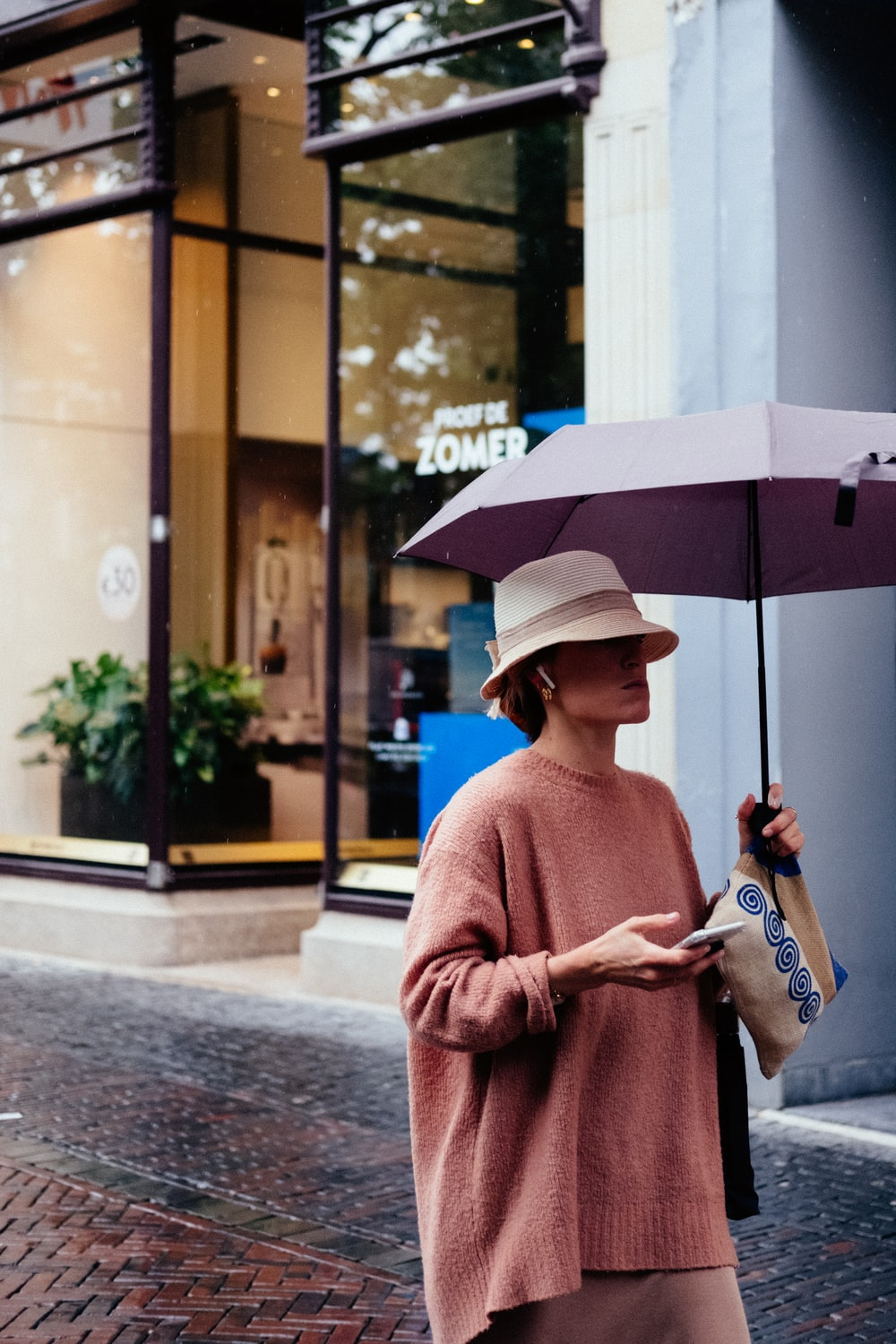 woman holding smartphone and umbrella while walking near building
