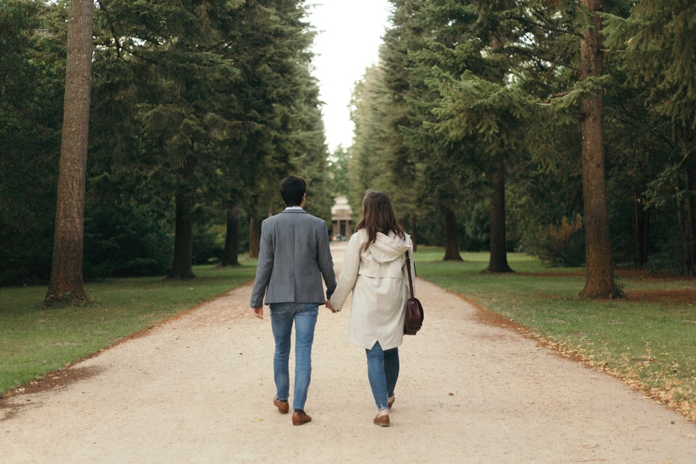 man and woman walking between trees