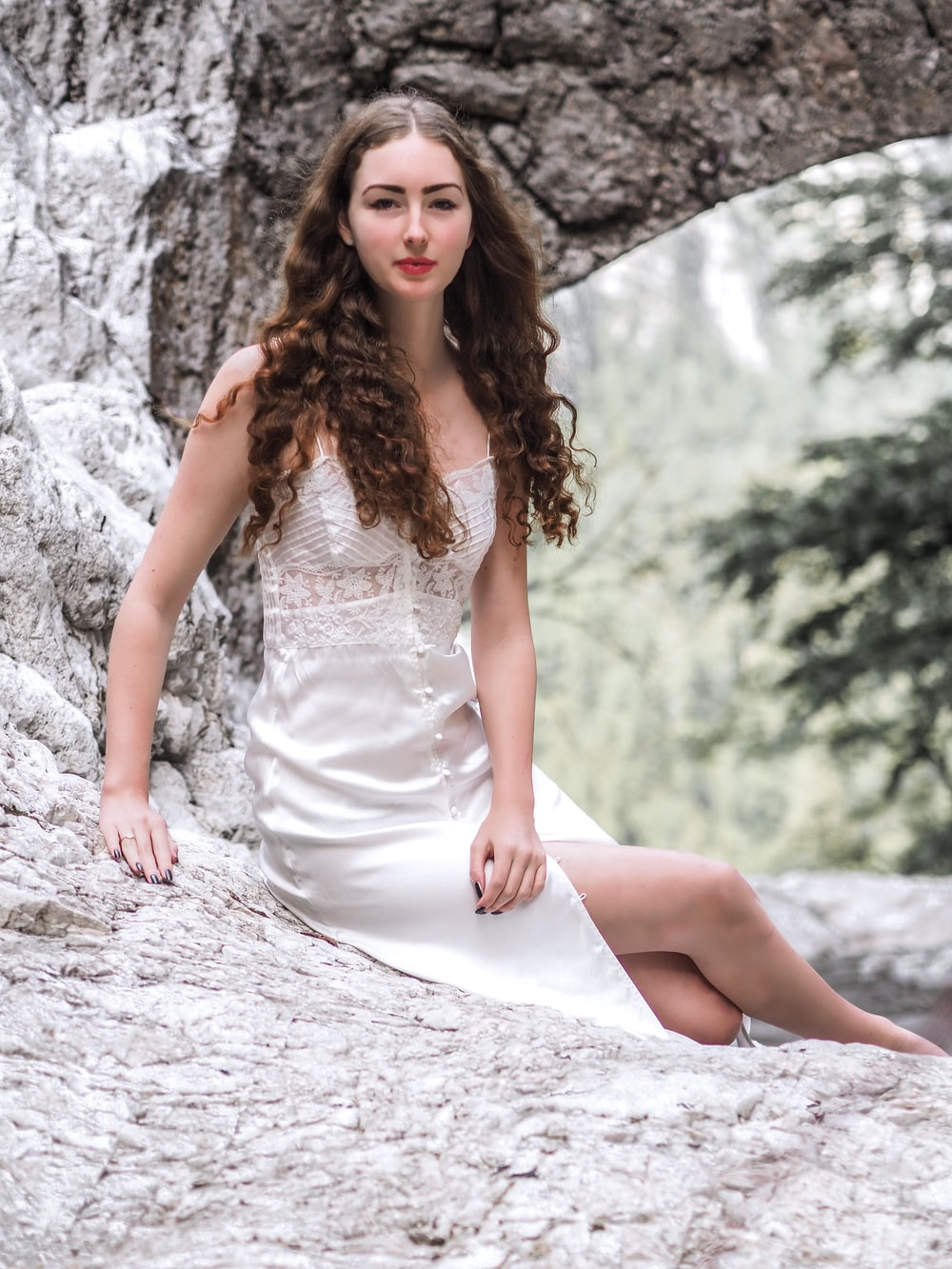 smiling woman in white button-up dress sitting on rock