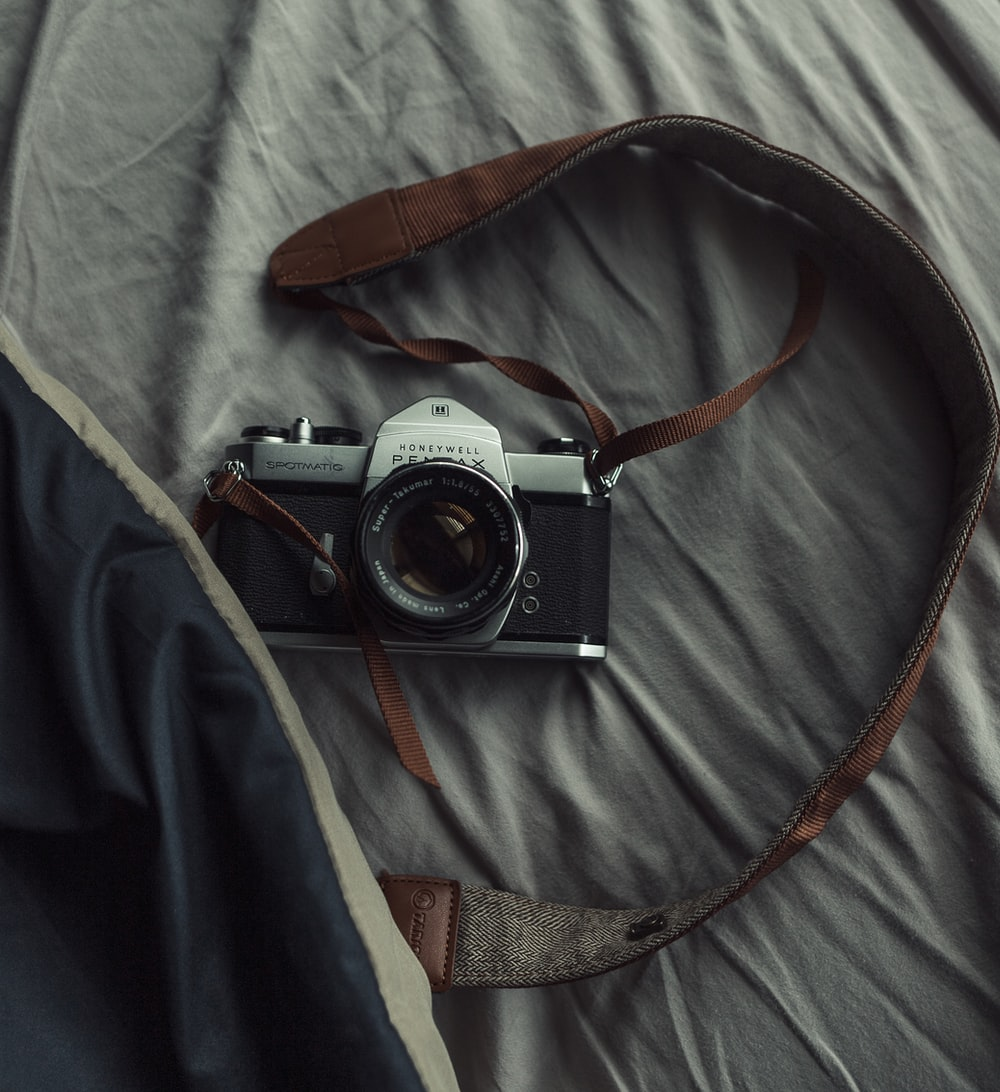 black and grey Pentax camera on bed