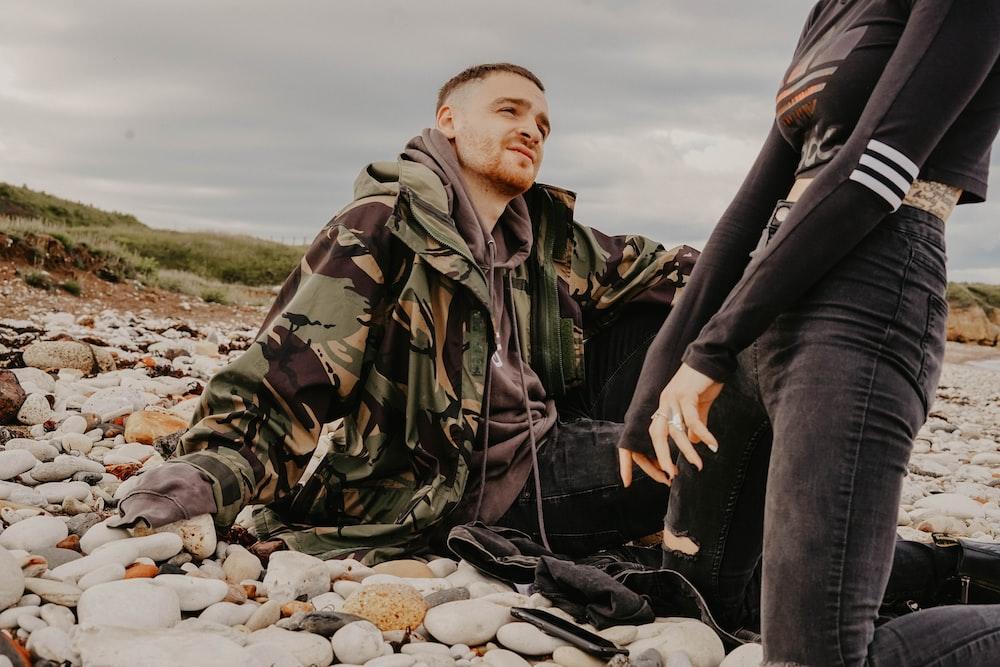 woman kneeling on stones beside man in camouflage jacket