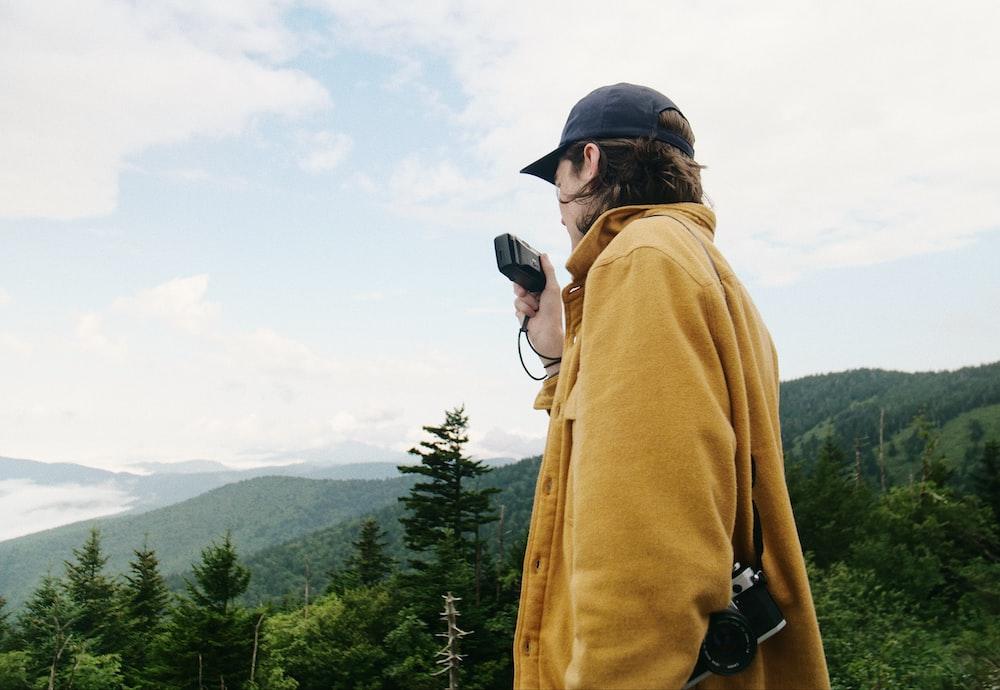 man wearing yellow coat with camera