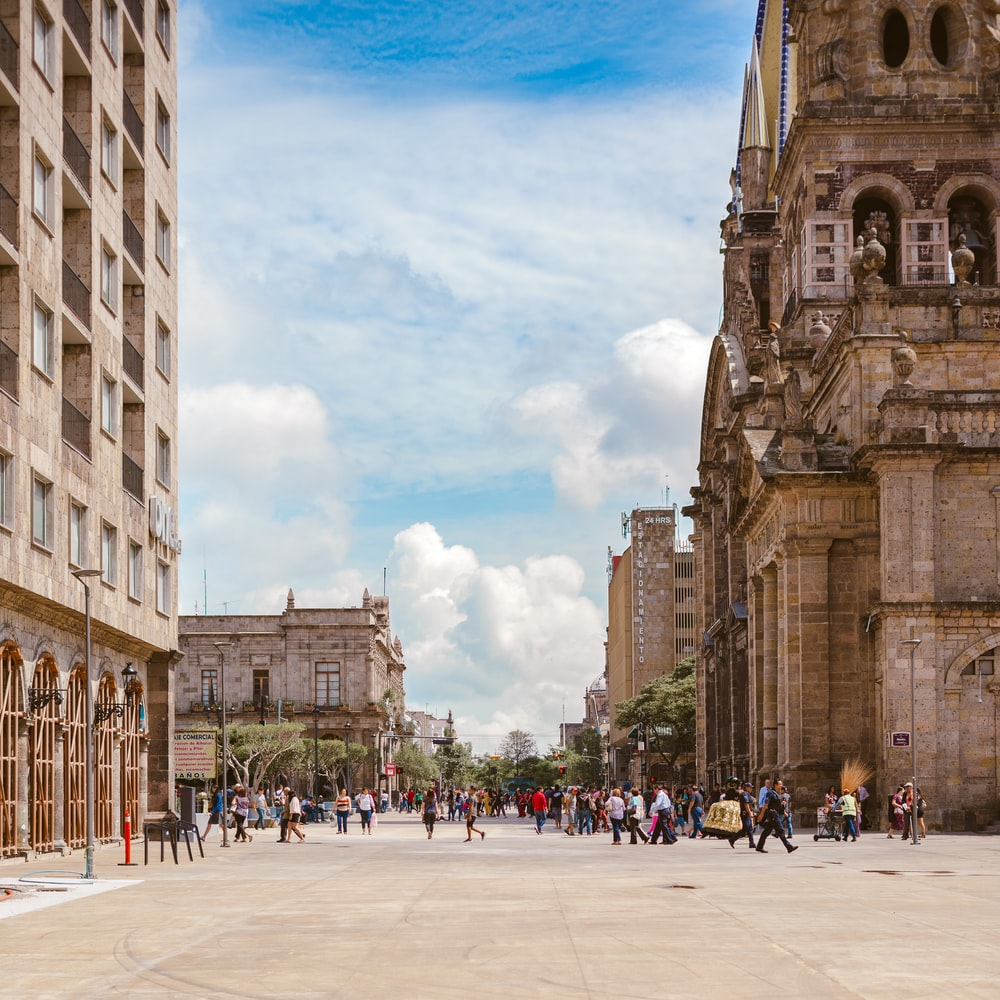 people walking near brown ancient cathedral under white and cloudy skies