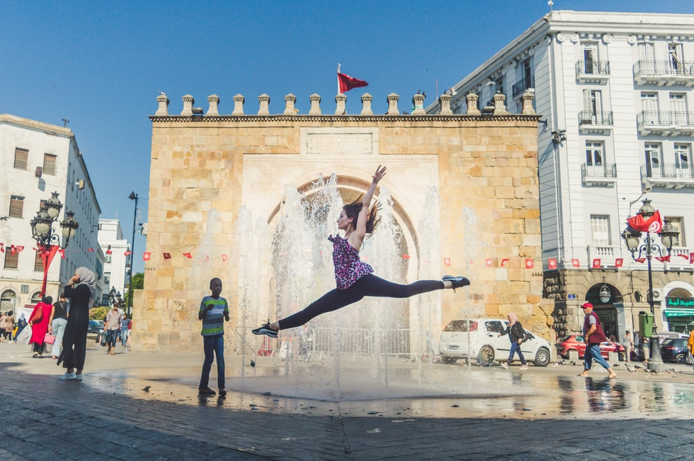 woman jumping in front of fountain during datime