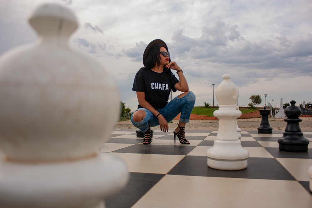 woman in black t-shirt and blue distressed denim jeans squatting on garden chess set