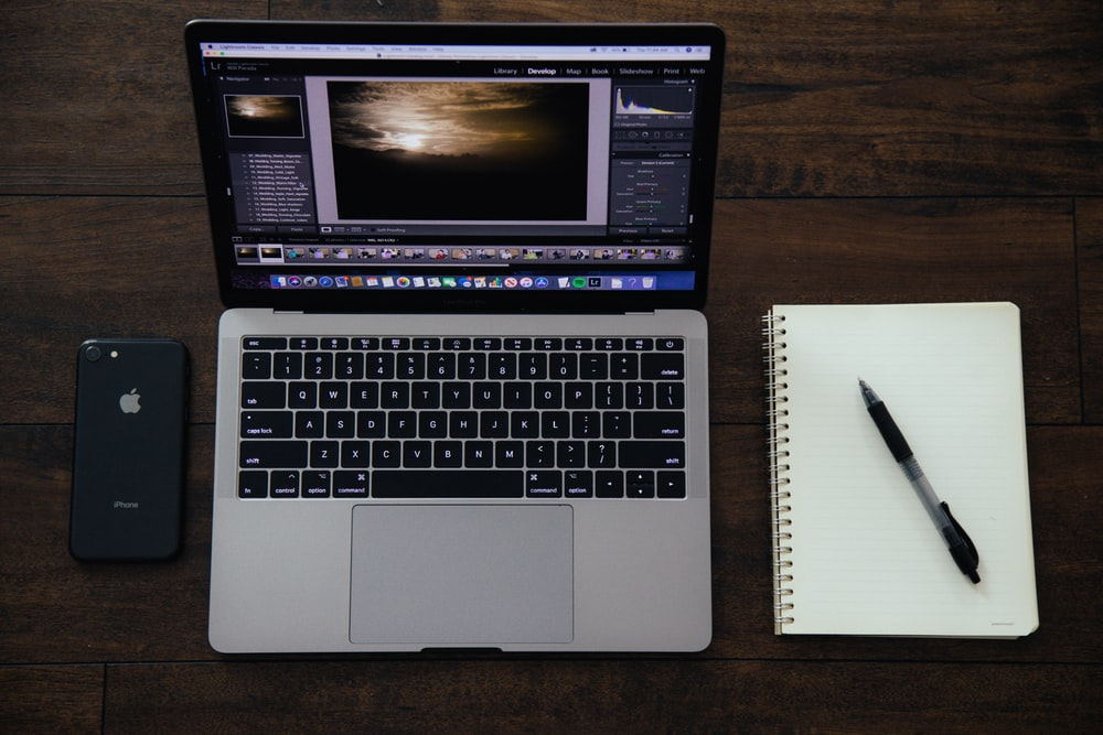 MacBook Pro near spiral notebook with pen on top and black iPhone 8