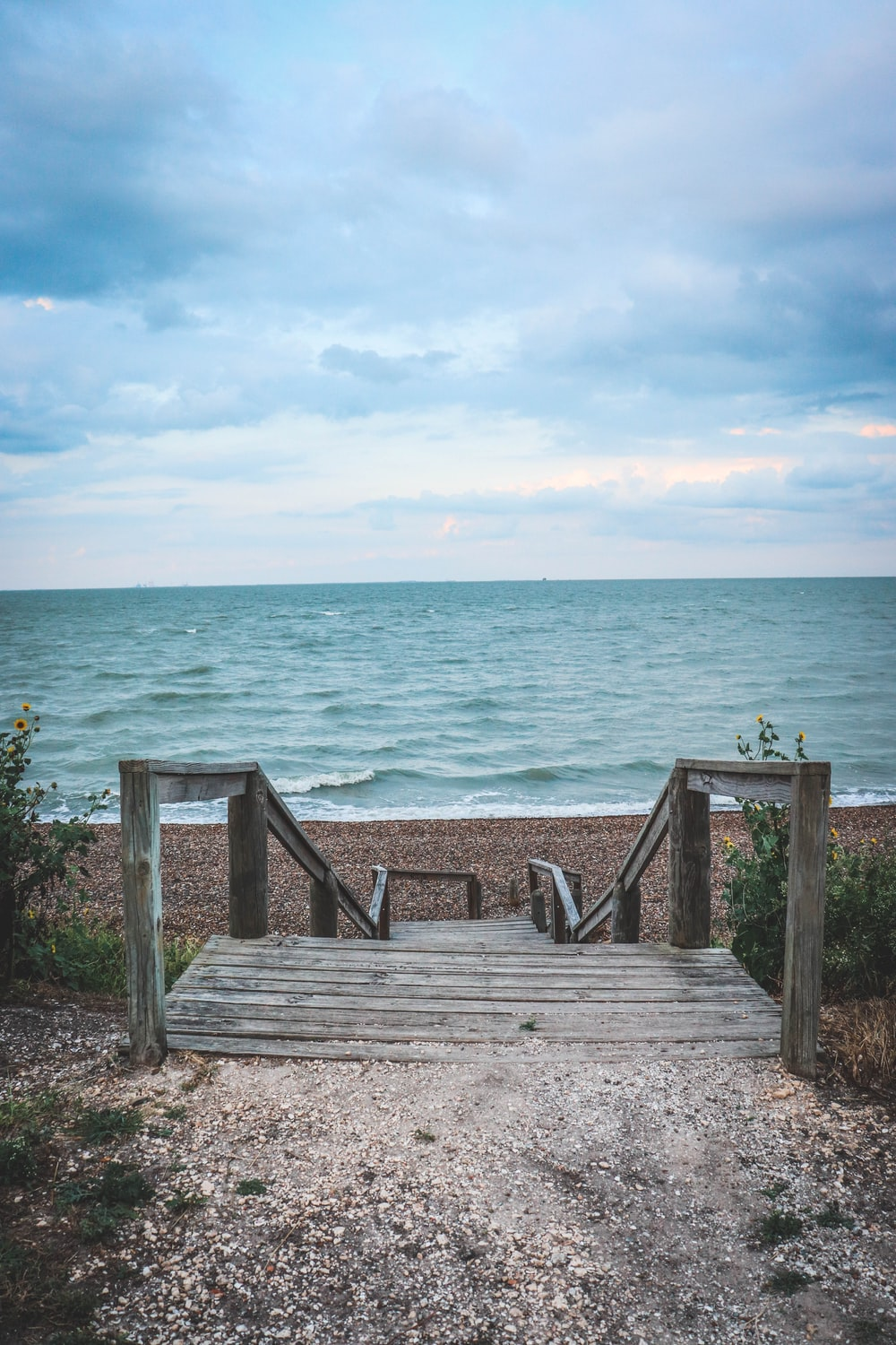 grey wooden stairs in front of beach