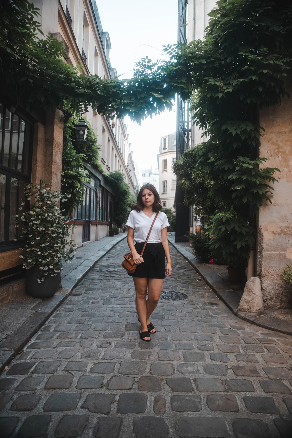woman standing on pavement in between buildings during daytime