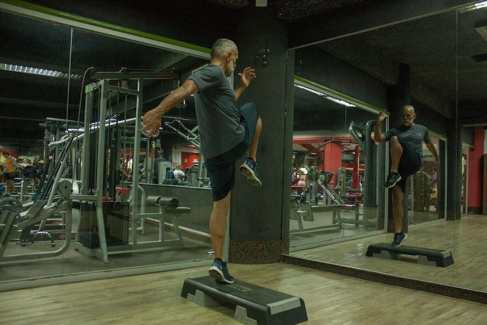 man wearing grey shirt and black shorts doing exercise