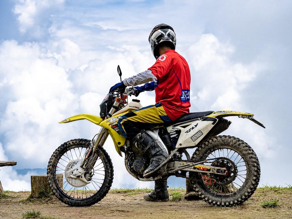 man riding on yellow and white dirt bike during daytime
