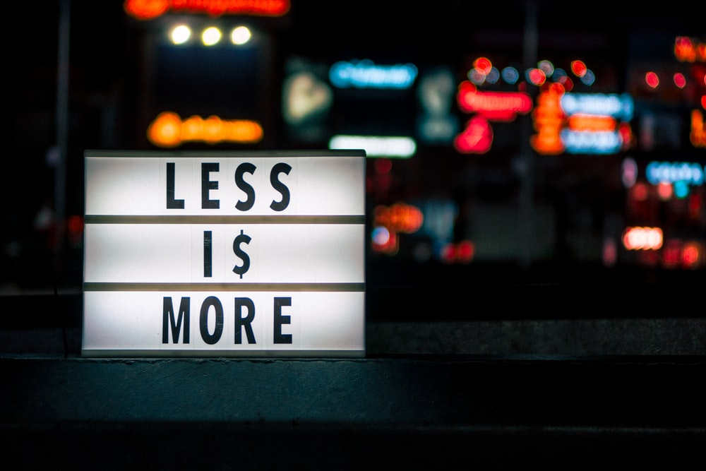 Less Is More signboard across blurry city lights