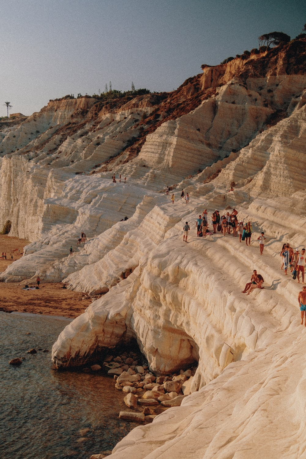 people in a rock formation near body of water during daytime