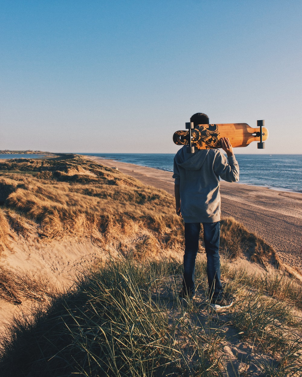 person holding a skateboard in a hill near body of water during daytime