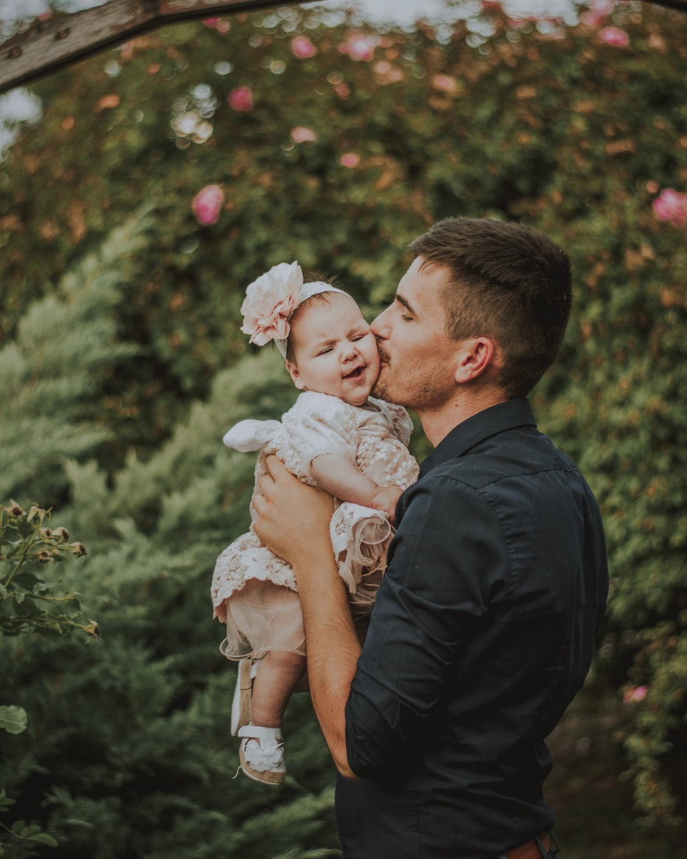 men holding a baby near plants during daytime