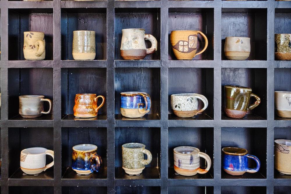 assorted-color mugs on rack