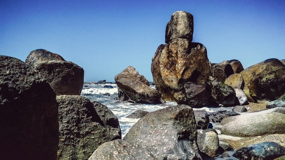 rock formations beside body of water at daytime