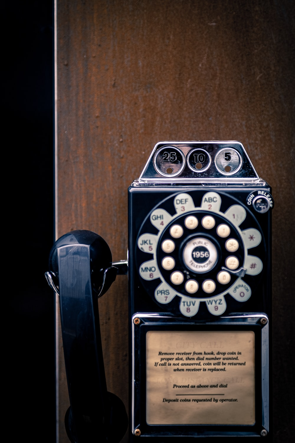 black and white wall telephone on brown wall